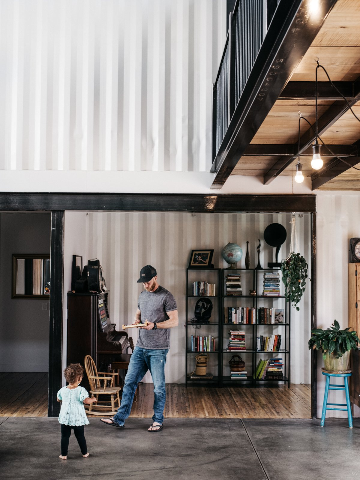 Living Room, Shelves, Concrete Floor, and Plywood Floor Regan worked with architect Joe Simmons and several tradespeople on the home.  Photo 8 of 13 in A Colorado Firefighter Built His Own Shipping Container Home, and Found a New Calling Along the Way