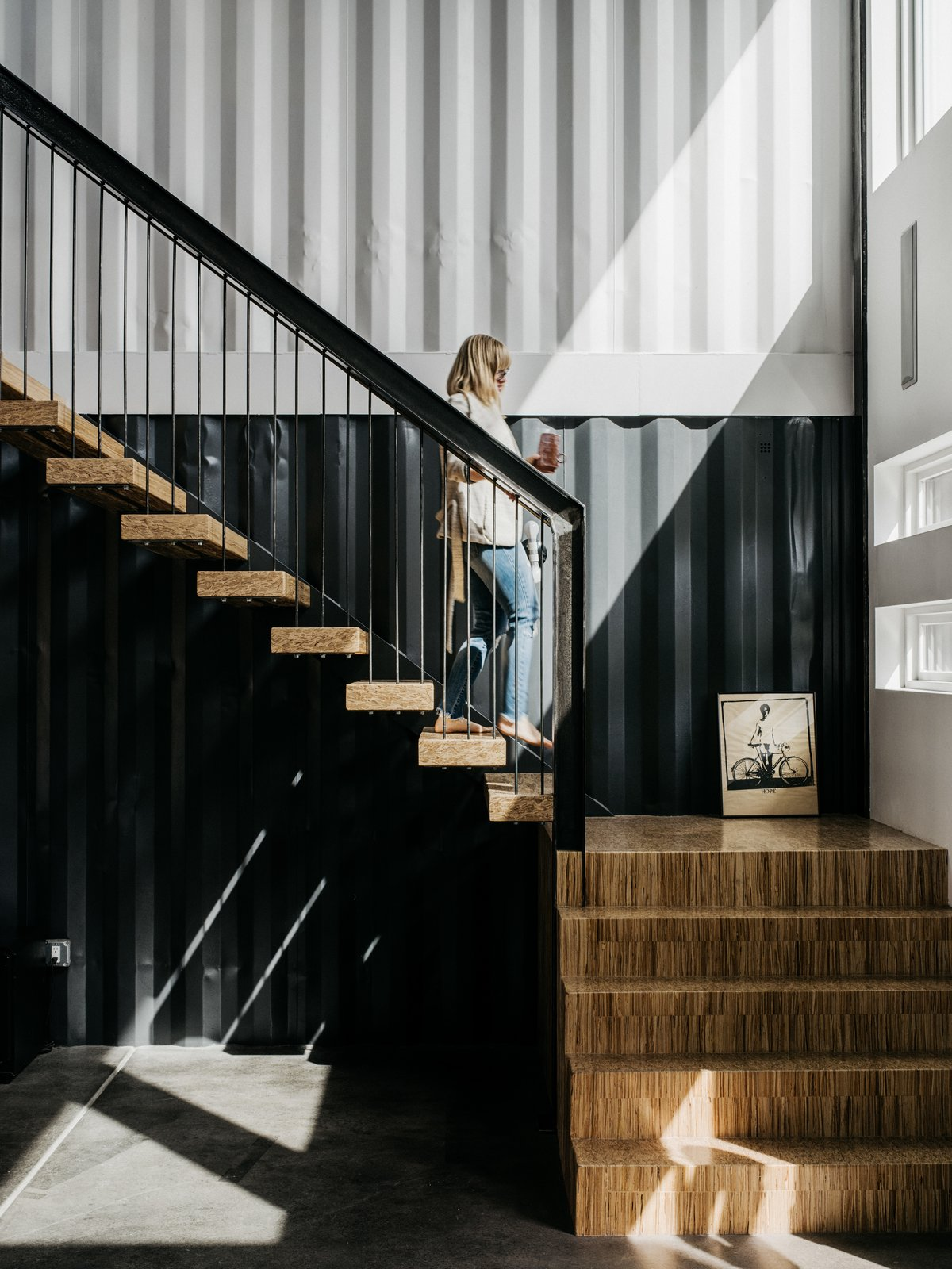 Staircase, Metal Railing, and Wood Tread In 2014, while recovering from a work-related injury, Denver-area firefighter Regan Foster started exploring the idea of shipping containers for a new house he was planning to build. Two years later, he and his wife, Libby, moved into a home made mostly of the giant metal bins, having done much of the work themselves. They share the residence with their year-old daughter, Evie, and Libby's mother.  Photo 1 of 13 in A Colorado Firefighter Built His Own Shipping Container Home, and Found a New Calling Along the Way