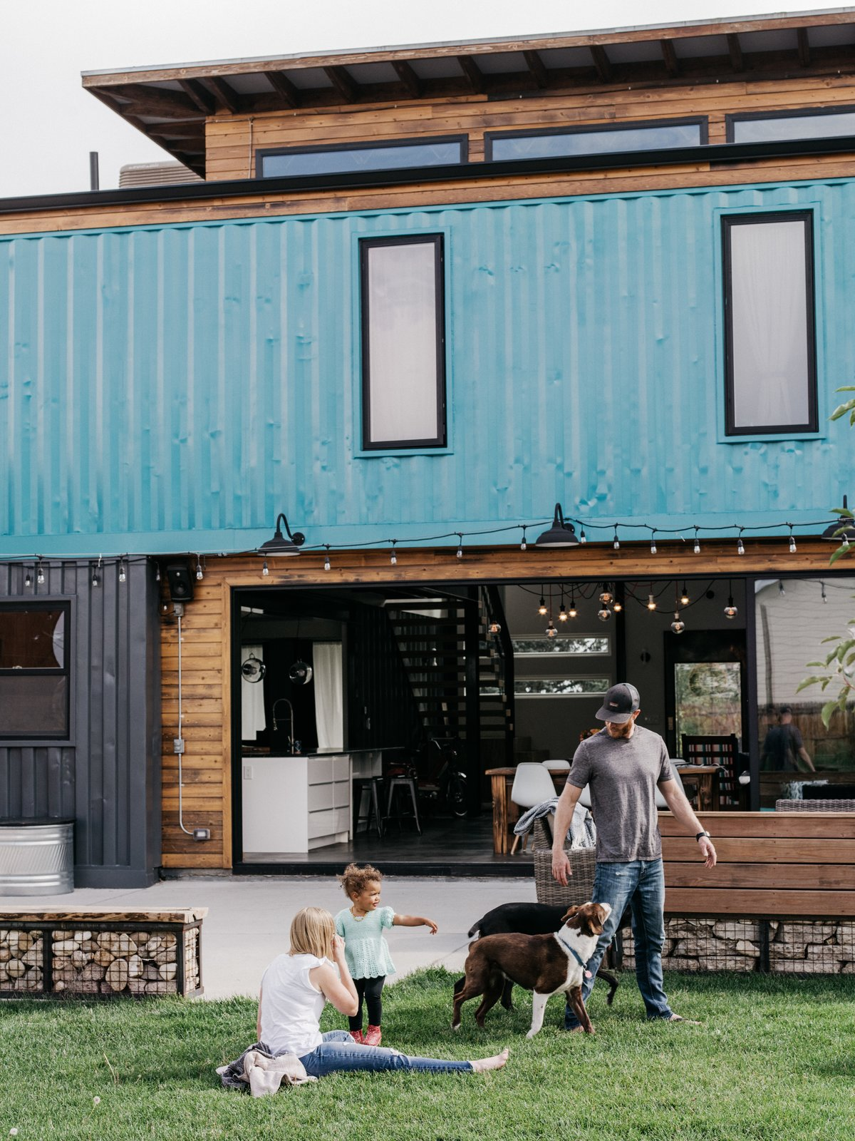 Outdoor, Hanging Lighting, Back Yard, and Grass Gabion walls define the back patio.  Photo 10 of 13 in A Colorado Firefighter Built His Own Shipping Container Home, and Found a New Calling Along the Way