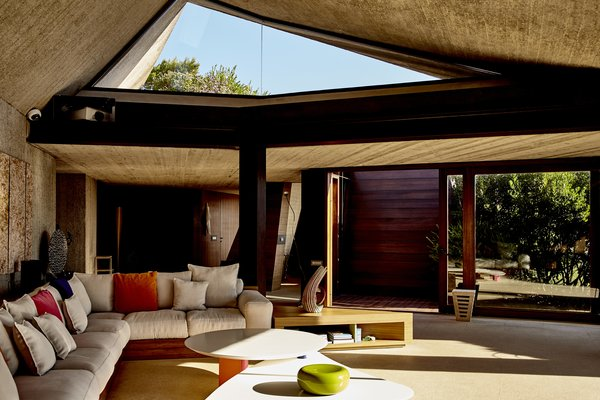 Canted asymmetrical ceilings and a mix of concrete, steel, and iroko wood define the main living area.
