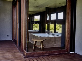 In the master bathroom, oversized windows and an Agape mirror pull the outside in.