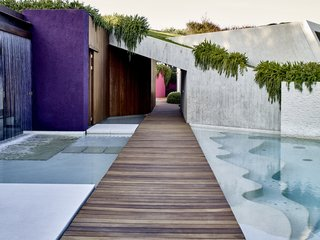 A new basalt walkway with iroko decking glides between a waterfall cascading off Villa 2 and a pool with squiggly steps.