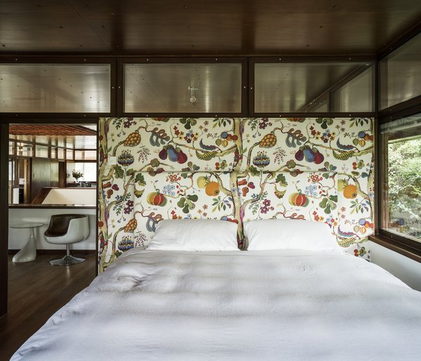 "In the master bedroom, the owners aligned ""Vegetable Tree,"" a 1940s wallcovering by Josef Frank that was reissued by Svenskt Tenn, behind a custom headboard in the same pattern."