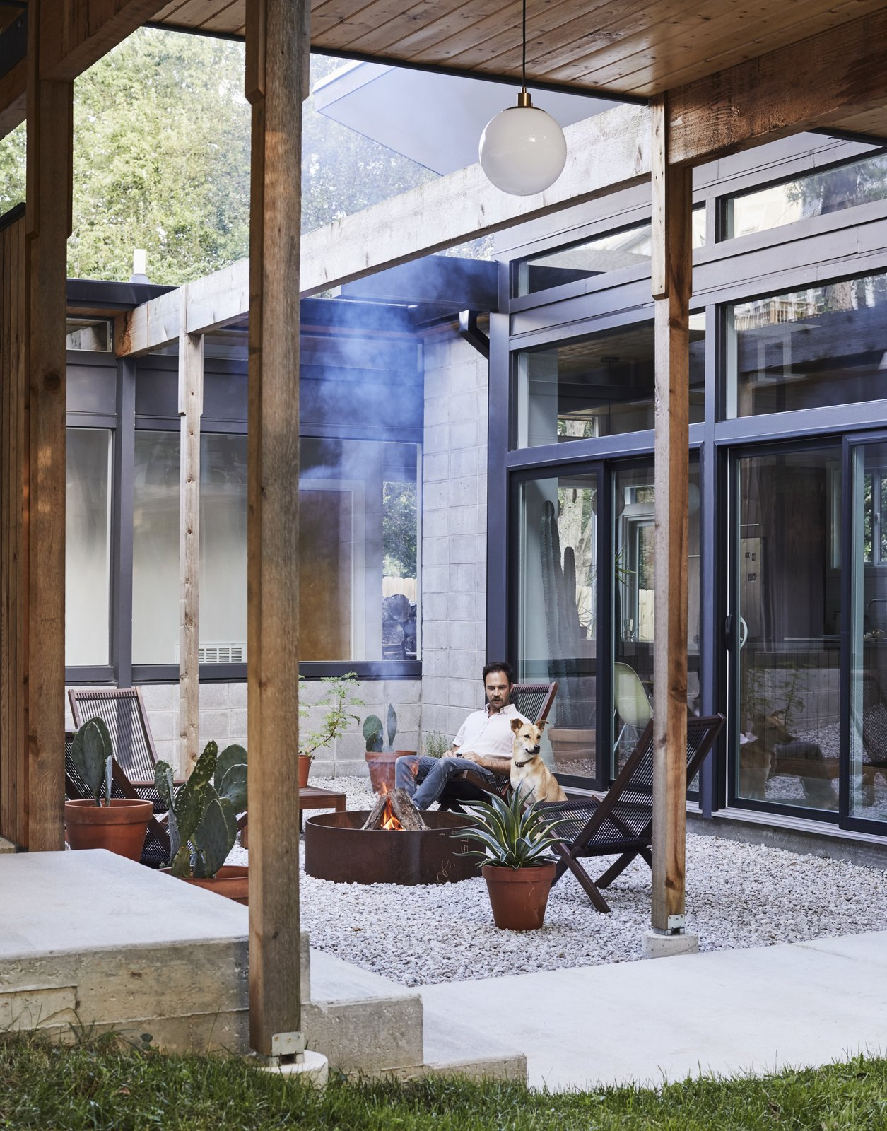 Outdoor, Walkways, and Hanging Lighting Bob sits in the entry courtyard with his dog, Goya.  My Photos from A Self-Taught Designer Builds a Midcentury-Inspired Home on a Budget
