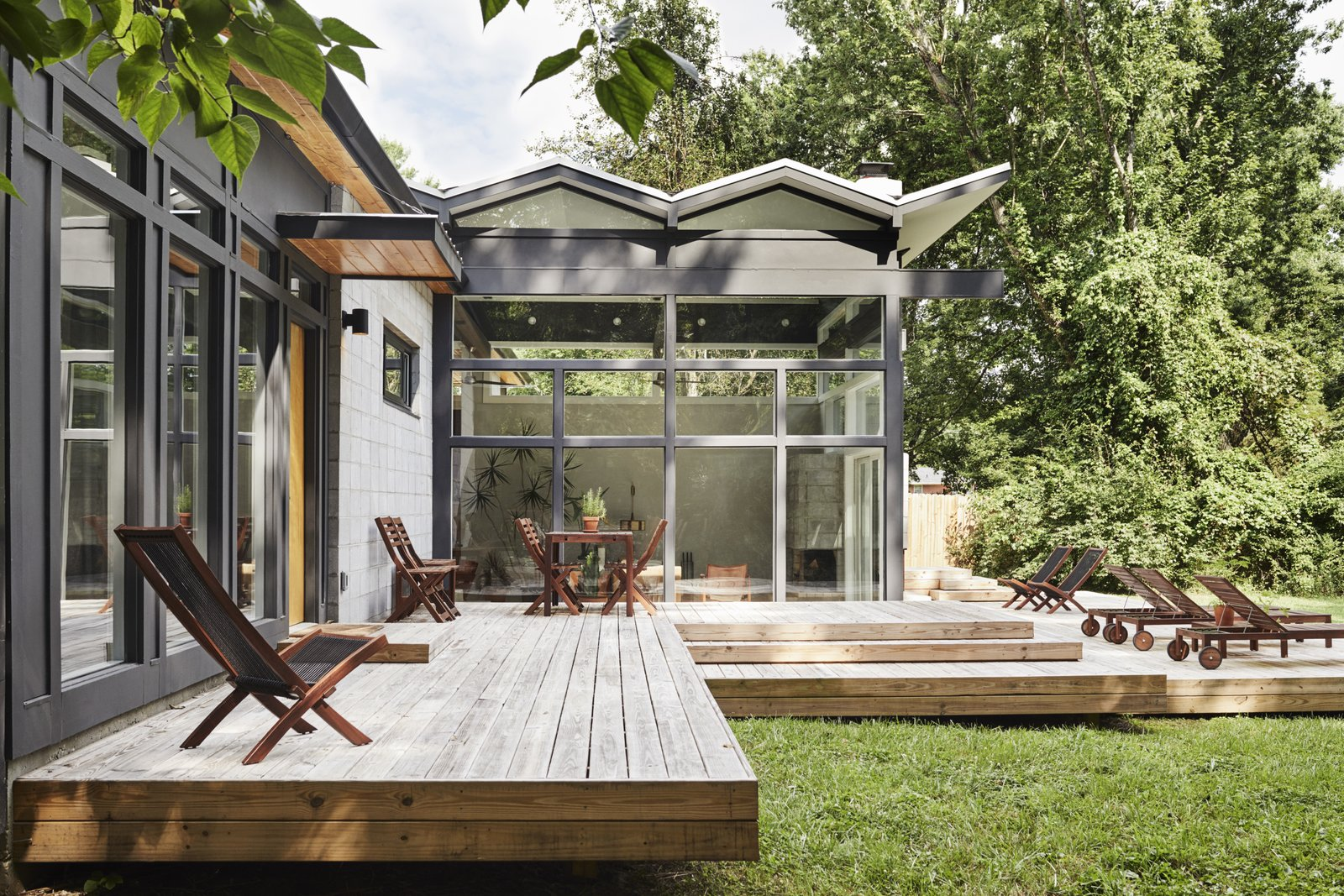 Outdoor, Back Yard, Wood Patio, Porch, Deck, and Grass An energy-efficient TPO membrane covers the living room's zigzag roof.  My Photos from A Self-Taught Designer Builds a Midcentury-Inspired Home on a Budget