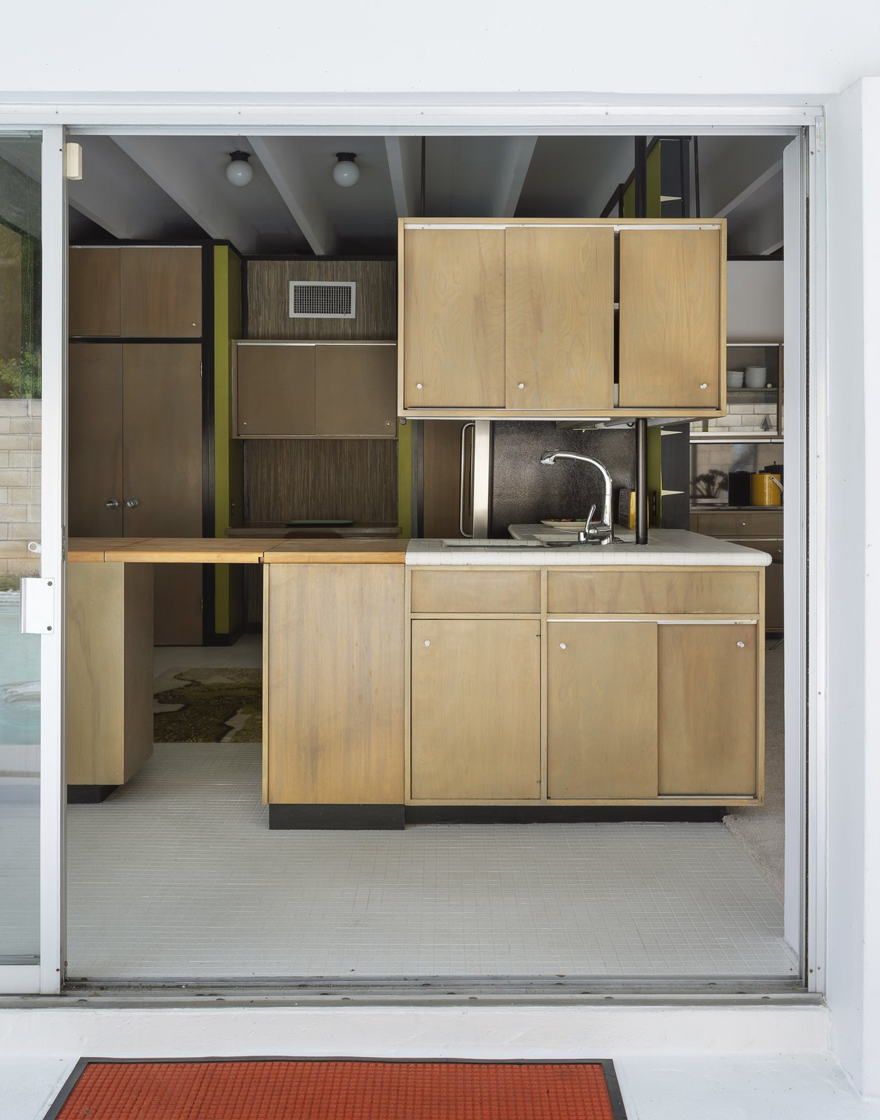 Kitchen and Wood Cabinet The kitchen cabinets are original.  The Ellison House from Pop Art, Street Art, and Space-Age Furniture Collide at a Painter's Midcentury Ranch Home in Florida