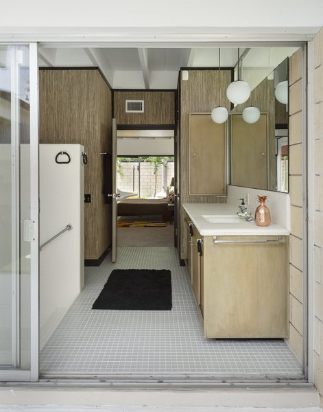 The master bathroom in this Gene Leedy-designed home in Florida is mostly original, with new grasscloth paper covering the formerly white walls. The midcentury modern bathroom vanity features muted wood and white tiles for a clean, modest look.