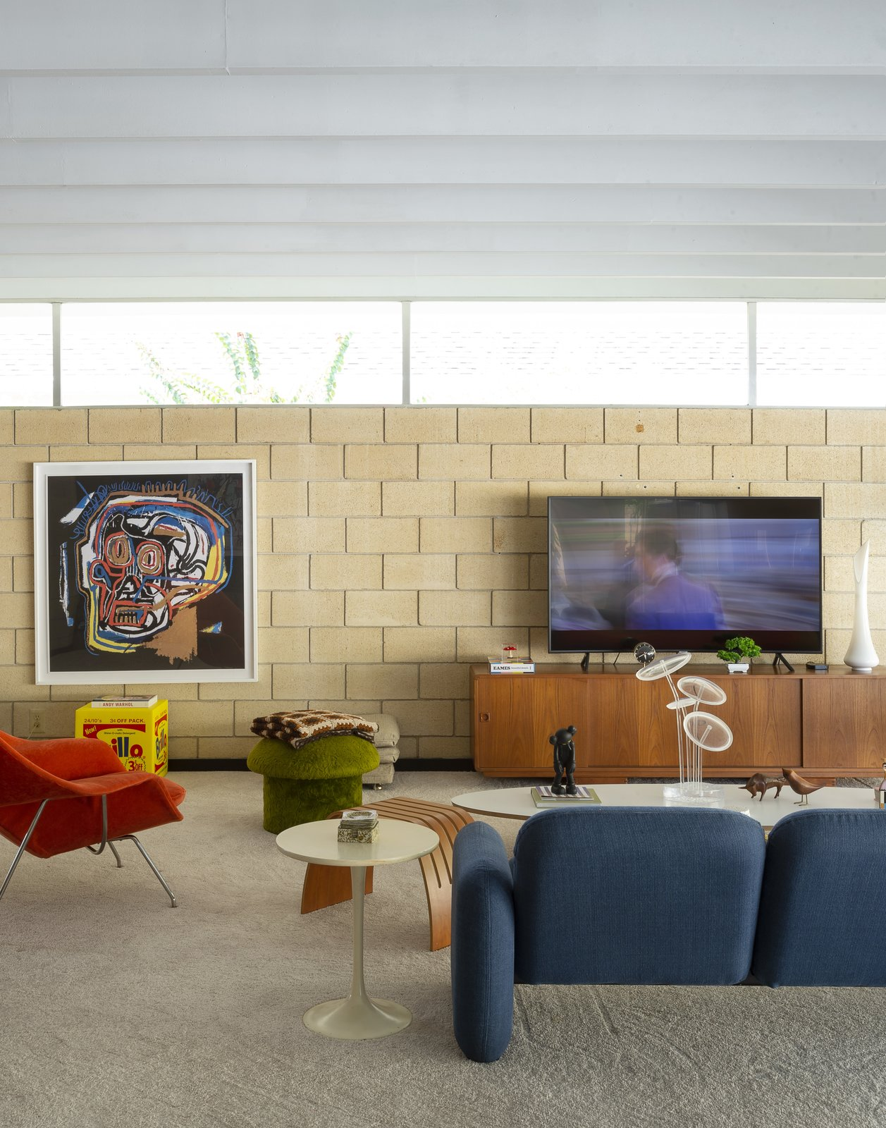"""Living Room, Coffee Tables, End Tables, Sectional, and Carpet Floor A print of Jean Michael Basquiat's """"Head  The Ellison House from Pop Art, Street Art, and Space-Age Furniture Collide at a Painter's Midcentury Ranch Home in Florida"""