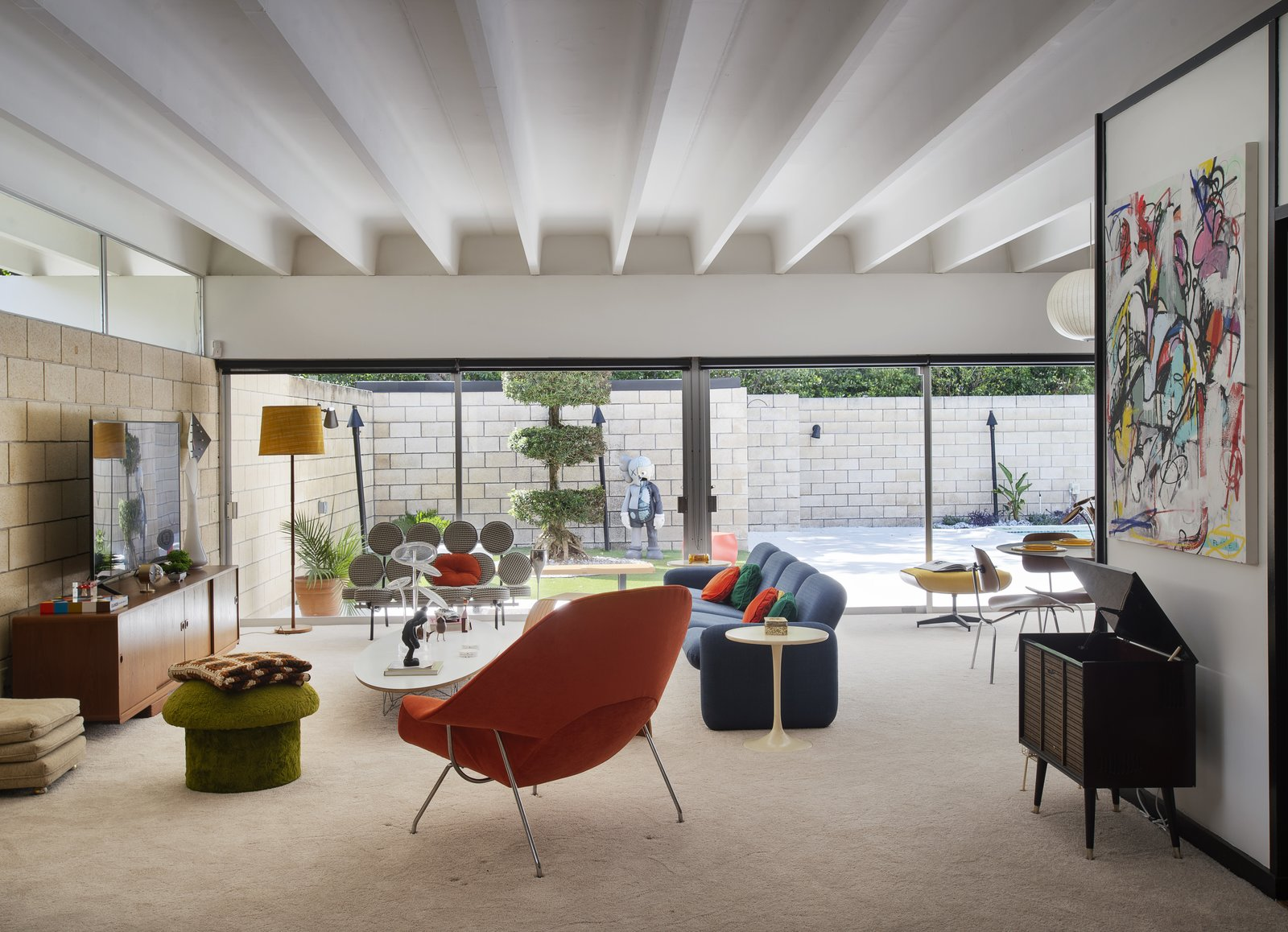 Living Room, Media Cabinet, End Tables, Carpet Floor, Chair, Sectional, Coffee Tables, and Floor Lighting The 1946 Womb Chair by Eero Saarinen by Knoll was reupholstered in Knoll Boucle Orange.  The Ellison House from Pop Art, Street Art, and Space-Age Furniture Collide at a Painter's Midcentury Ranch Home in Florida