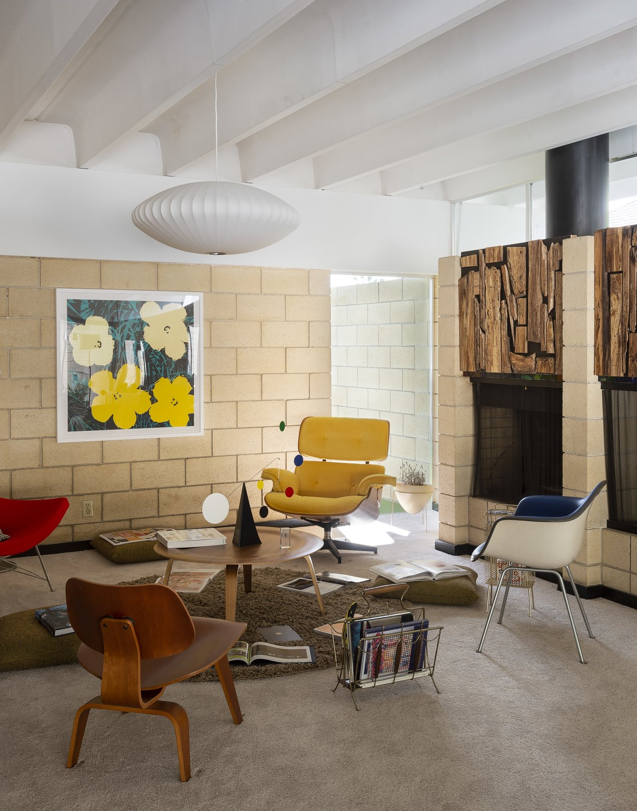"Living Room, Carpet Floor, Standard Layout Fireplace, Chair, Coffee Tables, and Ceiling Lighting Artist Christopher Florentino says his respect for Gene Leedy drove his update of the architect's 1963 Ellison Residence in central Florida: ""Being original is important to me. I don't want Gene Leedy to come here and be like, 'Damn, you killed my vision.'"" In the living room, George Nelson's Saucer Bubble pendant hovers over Eames classics, like an LCW chair, a Molded Fiberglass armchair, and a Molded Plywood coffee table. Christopher found the lounge, an Eames replica, in a dumpster and couldn't let it go to waste. A Warhol print hangs from the sandstone block wall; the Ekko mobile is by Matthew Richards.  Photo 1 of 25 in Pop Art, Street Art, and Space-Age Furniture Collide at a Painter's Midcentury Ranch Home in Florida"