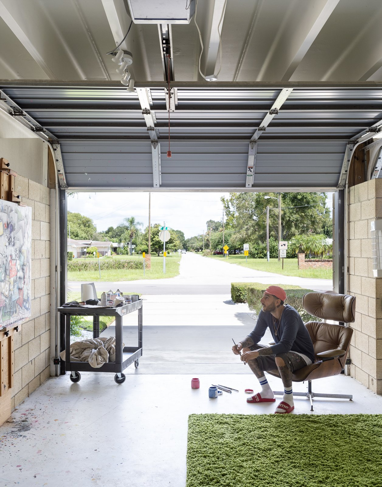 Garage and Garage Conversion Room Type Christopher, known professionally as Flore,  surveys a painting in his garage turned studio.  My Photos from Pop Art, Street Art, and Space Age Furniture Collide at a Painter's Midcentury Ranch Home in Florida