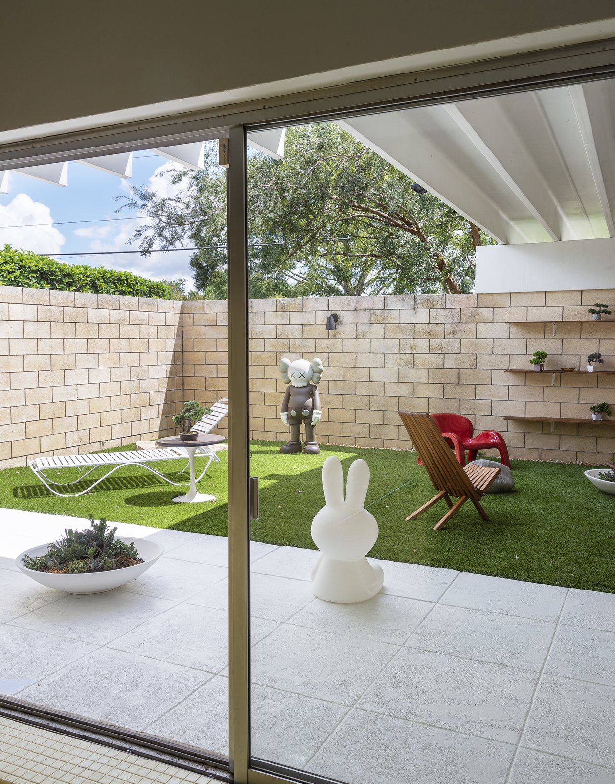 Outdoor, Small Patio, Porch, Deck, and Grass KAWS Companion Figure.  The Ellison House from Pop Art, Street Art, and Space-Age Furniture Collide at a Painter's Midcentury Ranch Home in Florida