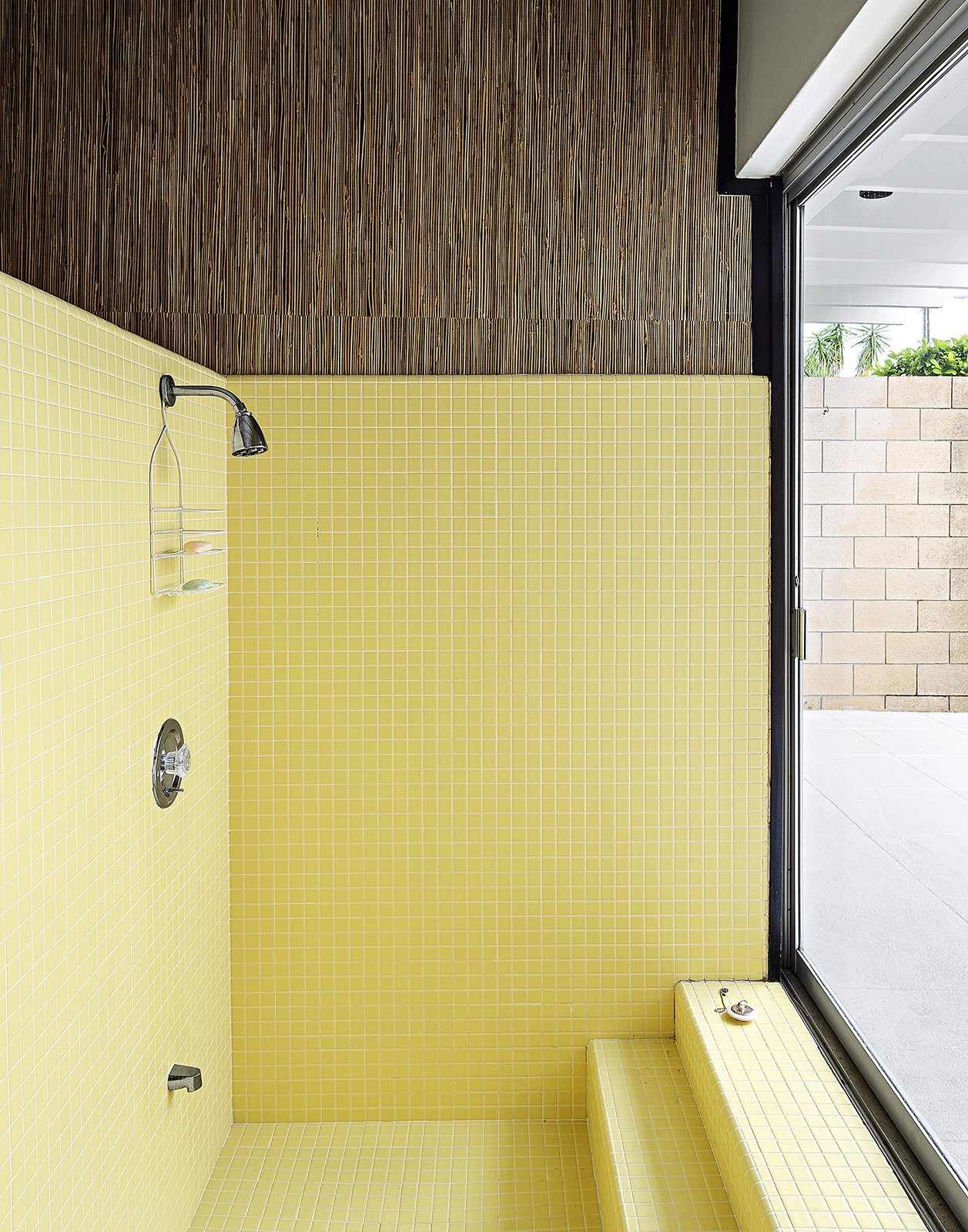 """Bath Room, Corner Shower, and Ceramic Tile Wall Bathroom Tile: The side-by-side bathrooms look out on a private courtyard through floor-to-ceiling sliding glass doors. They feature original tile in the sunken showers—one in butter yellow, the other in light gray. """"The tiles are heavy, real chunky, and of the period,"""" says Christopher. He had them completely restored, working alongside the tilers and filling cracks with a porcelain paint pen for two days straight. """"For something from 1963, they're really in immaculate shape,"""" he says.  My Photos from Pop Art, Street Art, and Space Age Furniture Collide at a Painter's Midcentury Ranch Home in Florida"""