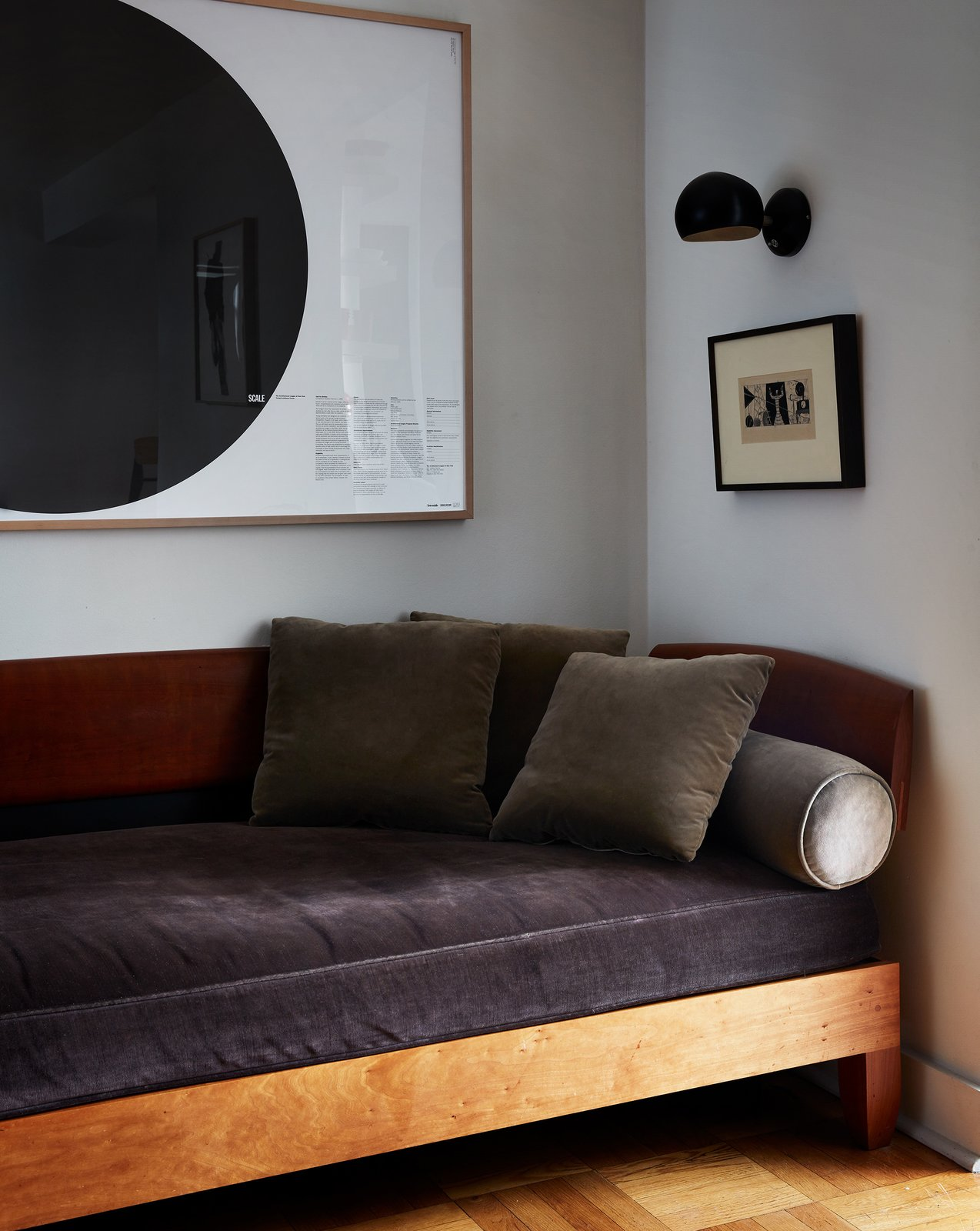 Living Room, Sofa, Wall Lighting, and Medium Hardwood Floor The velvet-upholstered daybed is a custom design by Chris Lehrecke.  My Photos from Two Magazine Creatives Fit Graphic Art and Vintage Furniture In a Brooklyn Apartment