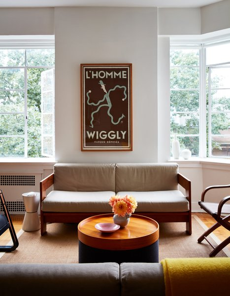 The coffee table is a Drum pouf with wood tray top, both by Softline for Design Within Reach and the yellow throw is by Raf Simons for Kvadrat. On the wall is a silkscreened L'Homme Wiggly poster by Greg Clarke.
