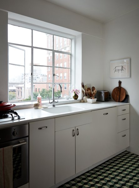This compact Brooklyn kitchen features a white Corian counter and integrated sink, IKEA cabinets with custom pulls, and geometric floor tiles in black, white and green from a collaborative series by Heath and Dwell. Black appliances pull the look together nicely.