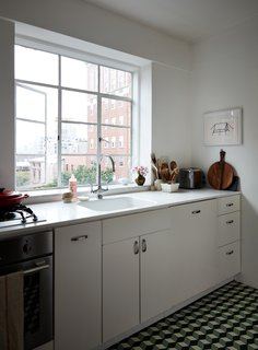 The kitchen features a white Corian counter and integrated sink, IKEA cabinets with custom pulls, and geometric floor tiles from a collaborative series by Heath and Dwell.