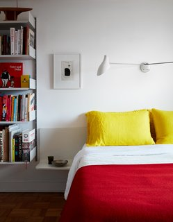 Even the bedding adheres to the color scheme, with yellow pillows from Merci in Paris and a red blanket from Best Made. The sconce is by David Weeks Studio.