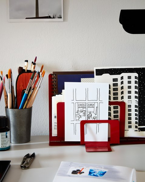 A sketch Nicholas drew of his office at The New Yorker stands in front of an illustration he made of their building.