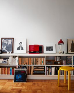 A red Crosley turntable sits on top of a custom shelving unit in the living room. The use of primary colors, also seen in the yellow Stool 60 by Alvar Aalto, is a nod to the Bauhaus, says Luise.
