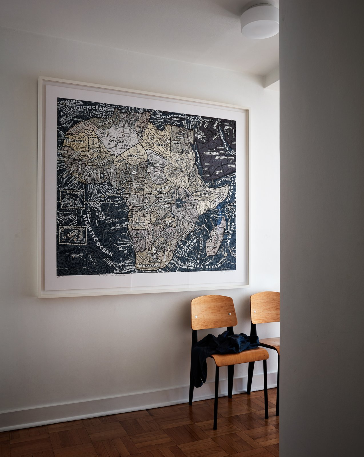 Hallway and Medium Hardwood Floor Pentagram designer Paula Scher gifted the couple one of her silkscreened maps.  My Photos from Two Magazine Creatives Fit Graphic Art and Vintage Furniture In a Brooklyn Apartment