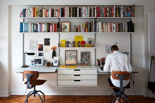 Some of the couple's favorite curios are displayed in their shared workspace, a Vitsœ wall unit. The Tab T lamps are by Flos.