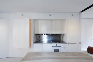"""German architect Julian von der Schulenburg did a complete overhaul of a 1901 townhouse in Ridgewood, Queens. The kitchen is part of an """"inhabitable wall"""" that holds the master bath, a mud room, a toilet, and a small  tub, accessible through a raised door."""
