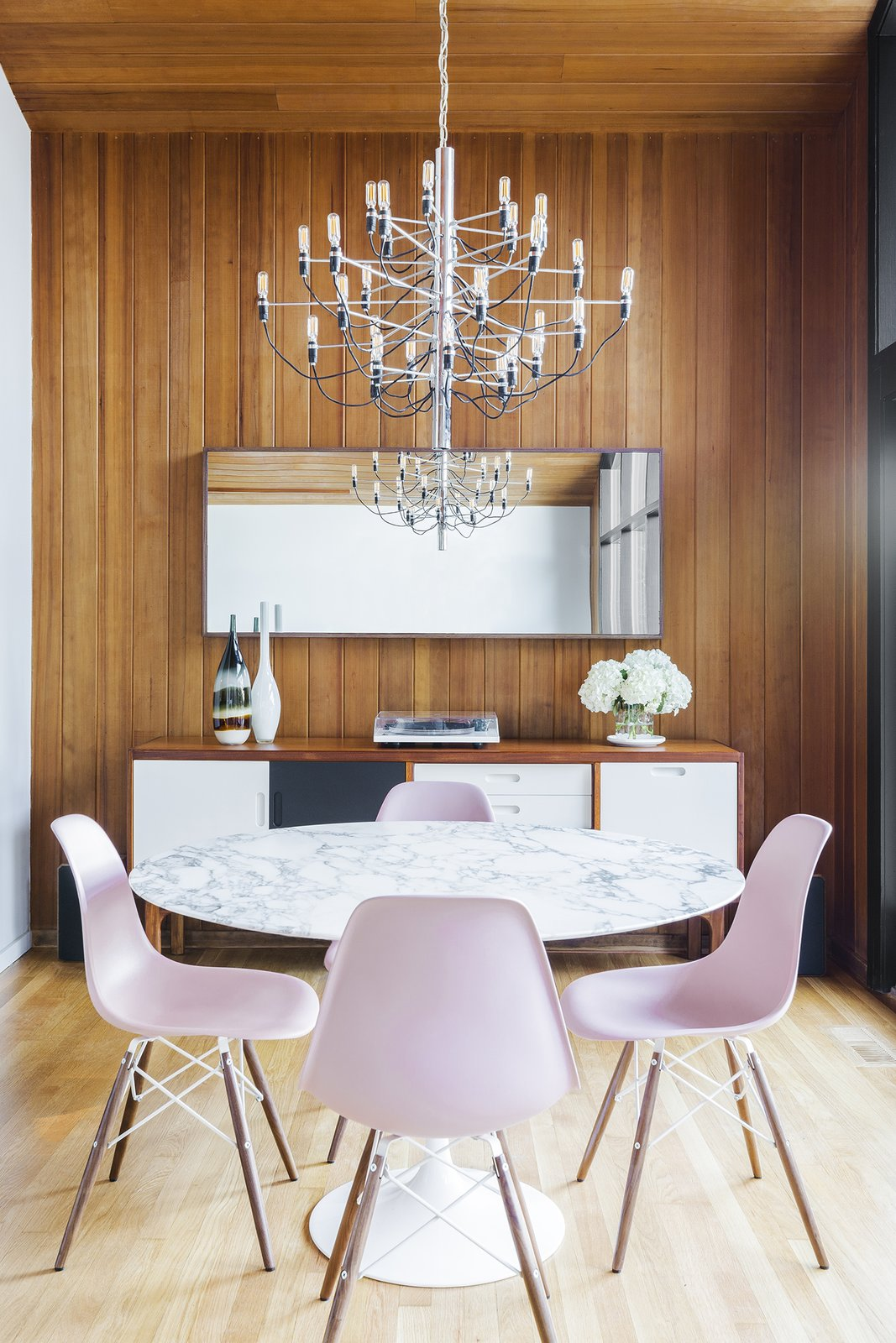 Dining Room, Chair, Table, Light Hardwood Floor, Pendant Lighting, and Storage In the dining room, a marble-topped Saarinen table is surrounded with pink Eames chairs.  Photo 6 of 21 in Before & After: A 1954 Midcentury in Portland Is Stunningly Revived