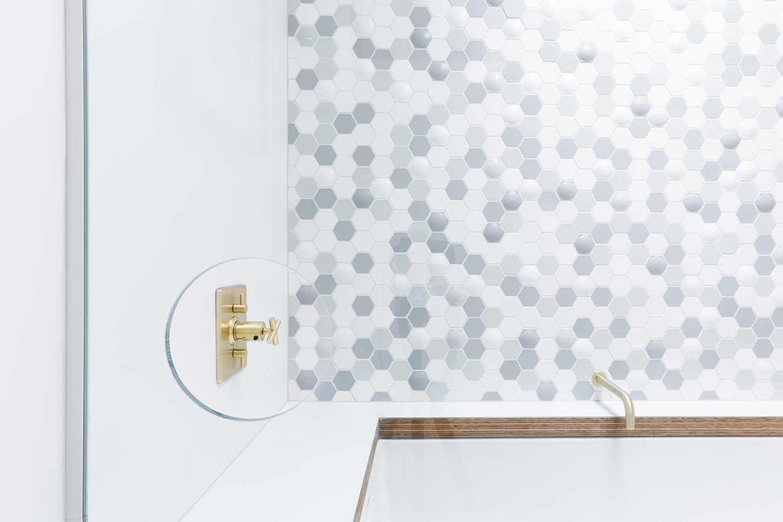 """Bath, Enclosed, Alcove, and Soaking A thoughtful cut-out in the glass enclosure allows people to reach the faucet without being sprayed by the shower. """"It's a bit of a signature for us,  Best Bath Enclosed Alcove Photos from Before & After: A 1954 Midcentury in Portland Is Stunningly Revived"""