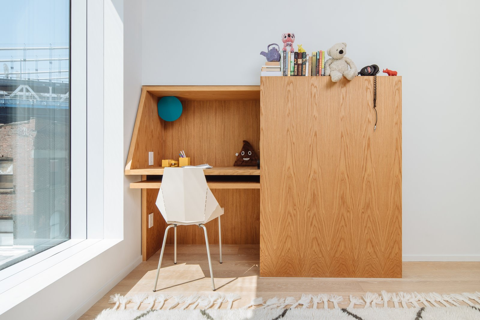 Kids, Pre-Teen, Bedroom, Chair, Neutral, Desk, Light Hardwood, Storage, and Rug The Real Good Chair is by Blu Dot.  Kids Chair Storage Light Hardwood Photos from A California Couple Give a Cookie-Cutter Brooklyn Condo Some Personality