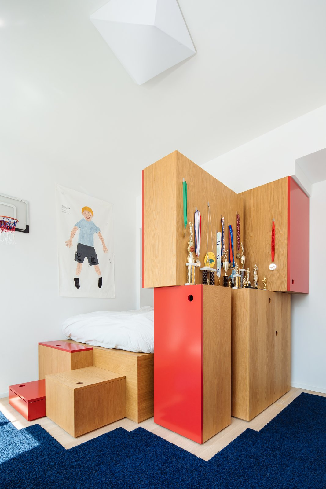"""Kids, Pre-Teen, Bed, Boy, Rug, Storage, Bedroom, and Light Hardwood In the boy's room, Dash Marshall designed a platform bed and multiple storage units, accented with red lacquer and arranged in a playful way. """"They're built-ins, but we didn't want them to look like built-ins,"""" says firm principal Ritchie Yao. """"They're more like stacked boxes.""""  Kids Storage Bed Photos from A California Couple Give a Cookie-Cutter Brooklyn Condo Some Personality"""