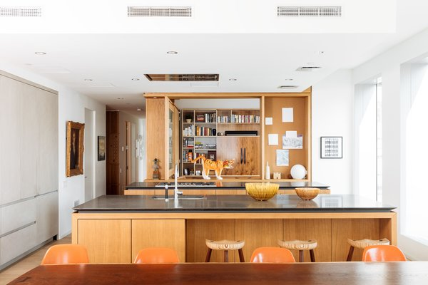 The media/guestroom is encased in white oak shelving and features a large translucent glass window. When it's open, the room connects visually to the kitchen. The stools and dining table are by Harlem Built; the Eames Molded Plastic chairs add a touch of color.