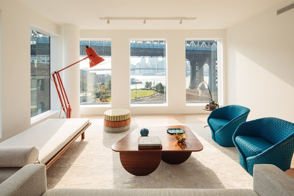 The light-filled living room, with its view of the Manhattan Bridge, gets extra wattage from an Anglepoise Giant lamp. A pair  of Talma armchairs by Moroso face  a walnut coffee table designed  by Dash Marshall and constructed  by Harlem Built. The daybed  was also fabricated by Harlem Built, from a drawing by Rachel.