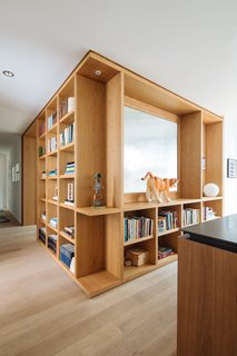 Custom white oak shelving separates the media/guestroom from the kitchen.