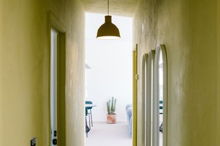 A chartreuse-colored corridor leads to the main living space. A Muuto pendant hangs above a series of Menu Oval Mirrors.