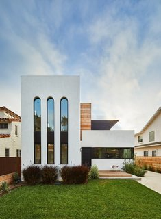 The building's crisp, white facade nods to the neighboring white stucco homes that were constructed in the 1920s and 1930s. The elongated arched windows give the exterior a 1920s Art Deco feel.