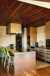 The kitchen features a mix of rammed-earth walls, strandboard-and-bamboo cabinets, and stainless steel counters. The appliances are by Fisher & Paykel, the faucet is by Plumbline, and the pendants are by Bruck.