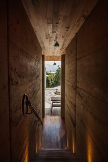 """A staircase lined with earthen walls leads from the entrance to the lower-level living areas and courtyard. """"Rammed earth has a beautiful texture,"""" says Simpson. """"If you get oblique light across it, tiny shadows form. It's quite stunning."""" The handrail was designed by Nigel and made by English blacksmith Spencer Larcombe; the pendants are by Bruck."""