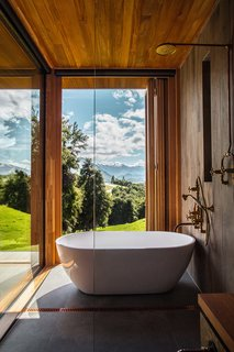 The master bathroom has a floor-to-ceiling windowed corner that holds a Belle freestanding tub by Progetto and in-wall fixtures by Copper Bath.