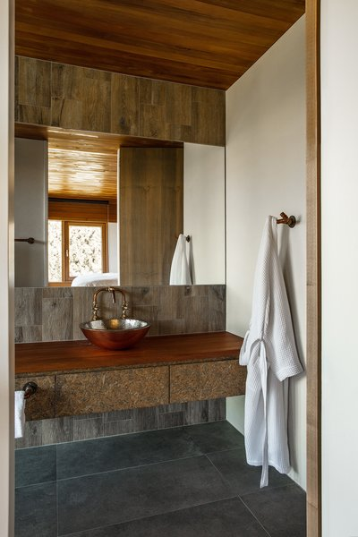 A vessel sink, also by Copper Bath, rests on the custom cedar-and-strandboard vanity.