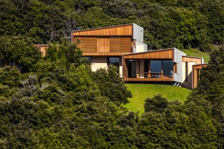 "Embedded in the side of a valley in New Zealand's Southern Alps, facing out over pristine Lake Wanaka, stands a new home meant to look as though it is part of the land around it. ""It resembles the large schist rocks you see all over this region that are half-buried in the hillside and poke out at strange angles,"" says Andrew Simpson of WireDog Architecture, the Wellington-based firm that designed it."