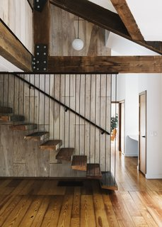 Floating against birch paneling, the main stair incorporates treads salvaged from old barn wood.