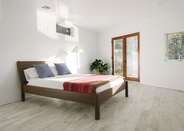 """""""The bedroom count stayed at three, but we added a new studio/playroom and converted one of the original bedrooms into a family room,"""" says Erik. Radiant-heated ceramic tiles warm the master bedroom on cold days. The bed and pillows are from IKEA."""