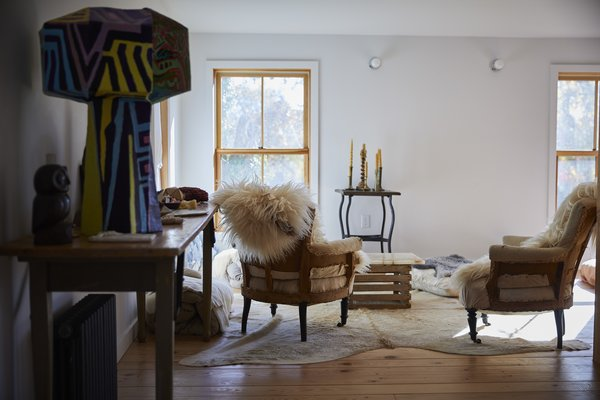 Vintage armchairs covered in sheepskin are arranged around a crate table on the second floor.