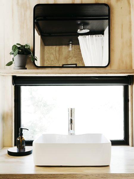 The bathroom's plywood counter, which supports a vessel sink by Fine Fixtures, has a matte polyurethane finish; the flower pot is by Hay and the mirror is from Target.