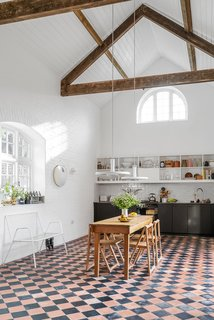After: When designer Michael Corsar converted a late Victorian utility building in Suffolk into a home for his friend Sandy Suffield, he kept the charming features, like the 17-foot ceilings, while making the space habitable after years of neglect. Deben Joinery built the kitchen cabinetry. The vintage Optima pendants are by Danish designer Hans Due.