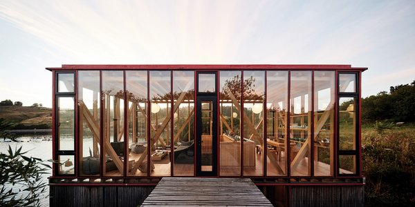 In Chile's Chiloé Archipelago, architect Guillermo Acuña developed a 12-acre island for his friends and family to unwind, first with a boathouse, later with pathway-connected cabins at the water's edge. Design details include glazed walls, eco-friendly pine, and a bright red palette that calls to mind the intensely colored chilco flowers that bloom here come spring and summer.