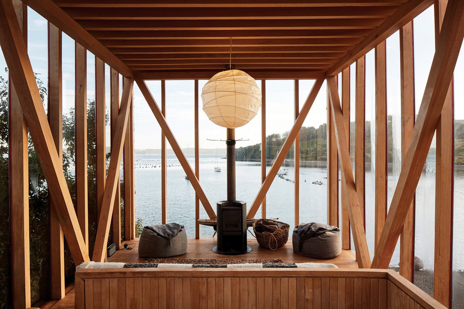 Living, Sofa, Pendant, Medium Hardwood, Wood Burning, and Chair The upper floor of one of the cabins features a wood-burning stove, beanbag chairs, and a hanging paper lantern.  Best Living Photos from An Architect in Chile Transforms an Uninhabited Island Into a Hideaway for Friends and Family