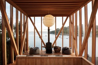 The upper floor of one of the cabins features a wood-burning stove, beanbag chairs, and a hanging paper lantern.