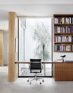 Facing another courtyard, an office nook features a Caesarstone countertop and walnut built-ins by Austin Wood Work.
